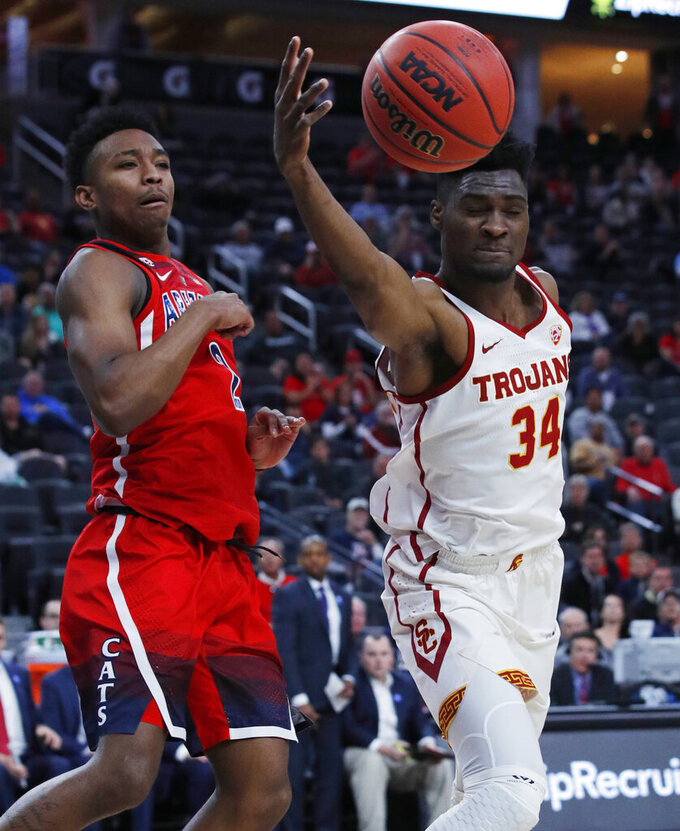 Southern California's Victor Uyaelunmo (34) and Arizona's Brandon Williams (2) vie for a rebound during the first half of an NCAA college basketball game in the first round of the Pac-12 conference tournament Wednesday, March 13, 2019, in Las Vegas. (AP Photo/John Locher)