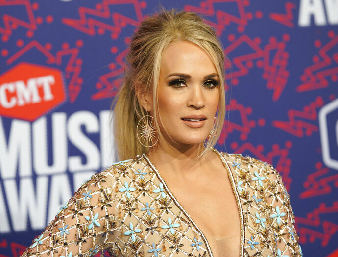 FILE- In this June 6, 2019 file photo, Carrie Underwood arrives at the CMT Music Awards at the Bridgestone Arena in Nashville, Tenn. On Wednesday, June 19, 2019, a songwriting team filed a lawsuit against the singer, the NFL and NBC, saying they stole a song and used it to introduce