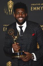 """Emmanuel Acho poses with the award for short form nonfiction or reality series for """"Uncomfortable Conversations with a Black Man,""""  on night two of the Creative Arts Emmy Awards on Sunday, Sept. 12, 2021, in Los Angeles. Acho wore a suit bearing the names of Black Americans killed at the hands of police. (Photo by Richard Shotwell/Invision/AP)"""