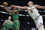 Boston Celtics guard Kemba Walker (8) drives to the hoop past Denver Nuggets center Nikola Jokic (15) in the second half of an NBA basketball game, Friday, Dec. 6, 2019, in Boston. Celtics forward Daniel Theis (27) looks on. (AP Photo/Elise Amendola)