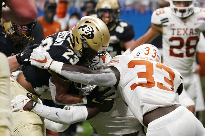 Colorado running back Jarek Broussard (23) is hit by Texas linebacker David Gbenda (33) as he runs for a touchdown during the first half of the Alamo Bowl NCAA college football game Tuesday, Dec. 29, 2020, in San Antonio. (AP Photo/Eric Gay)