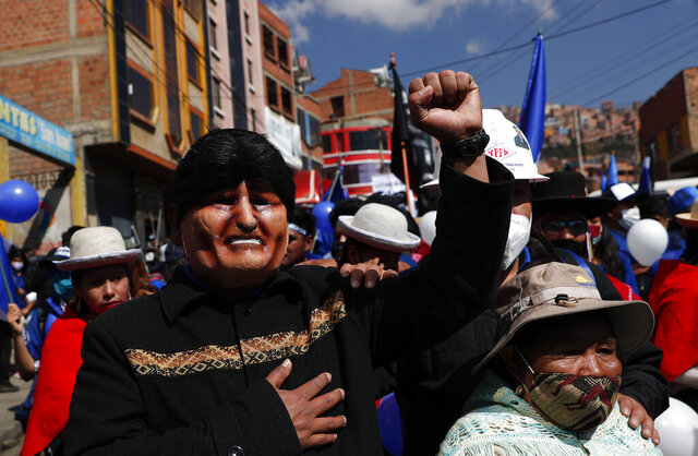 FILE - In this Sept. 19, 2020 file photo, a supporter, wearing a mask depicting former President Evo Morales, strikes a pose during a campaign rally for Luis Arce Catacora, the Bolivian presidential candidate for the Movement Towards Socialism Party, or MAS, in La Paz, Bolivia. MAS is the party founded by Morales who was ousted in November 2019, after several weeks of demonstrations that erupted over allegations of fraud in last year's October presidential election that Morales claimed to have won. (AP Photo/Juan Karita, File)