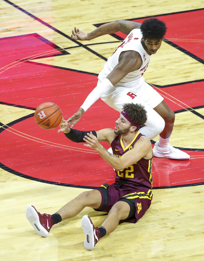 Minnesota guard Gabe Kalscheur (22) plays the ball from the floor as Rutgers center Myles Johnson (15) defends during the first half of an NCAA college basketball game Thursday, Feb. 4, 2021, in Piscataway, N.J. (Andrew Mills/NJ Advance Media via AP)