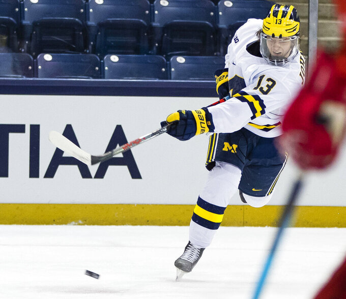 FILE- In this March 14, 2021, file photo, Michigan's Kent Johnson (13) shoots during an NCAA college Big Ten hockey tournament game against Ohio State, at the Compton Family Ice Arena in South Bend, Ind. Ann Arbor, Michigan, became a must-stop on the scouting trail because of a buzz-worthy Wolverines lineup featuring a trio of highly touted freshmen in defenseman Owen Power, and forwards Kent Johnson and Mathew Beniers. (Michael Caterina/South Bend Tribune via AP, FIle)
