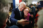 Democratic presidential candidate former Vice President Joe Biden takes a selfie during a campaign event on foreign policy at a VFW post Wednesday, Jan. 22, 2020, in Osage, Iowa. (AP Photo/John Locher)