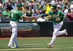 Oakland Athletics' Mark Canha, right, is congratulated by third base coach Matt Williams (4) after hitting a home run off Seattle Mariners' Tommy Milone in the fourth inning of a baseball game Wednesday, July 17, 2019, in Oakland, Calif. (AP Photo/Ben Margot)