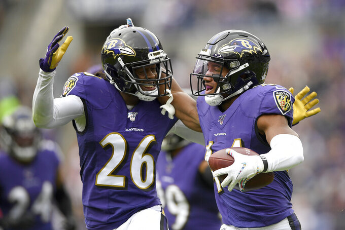 Baltimore Ravens cornerback Marlon Humphrey, right, celebrates his interception off a pass from Cincinnati Bengals quarterback Andy Dalton with teammate cornerback Maurice Canady (26) during the first half of a NFL football game Sunday, Oct. 13, 2019, in Baltimore. (AP Photo/Nick Wass)
