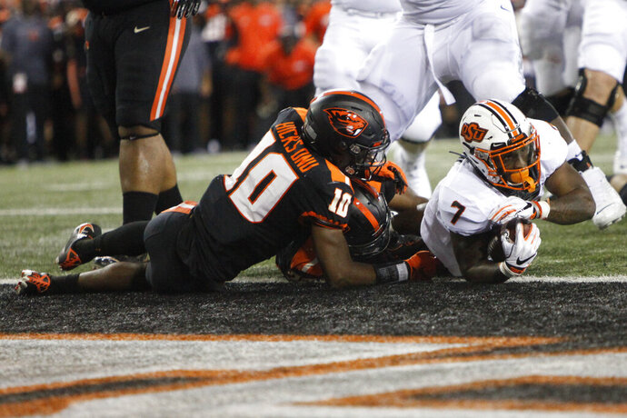 Oklahoma State running back LD Brown (7) narrowly makes it into the end zone for a touchdown despite defense from Oregon State defensive back Omar Hicks-Onu (10) and inside linebacker Omar Speights (36) during the first half of an NCAA college football game in Corvallis, Ore., Friday, Aug. 30, 2019. (AP Photo/Amanda Loman)