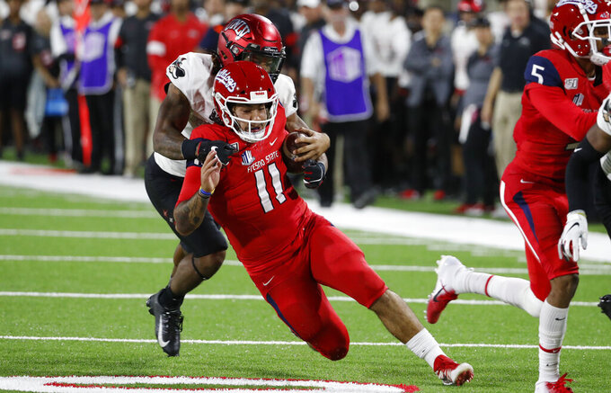 UNLV defensive back Evan Austrie tackles Fresno State quarterback Jorge Reyna during the first half of an NCAA college football game in Fresno, Calif., Friday, Oct. 18, 2019. (AP Photo/Gary Kazanjian)