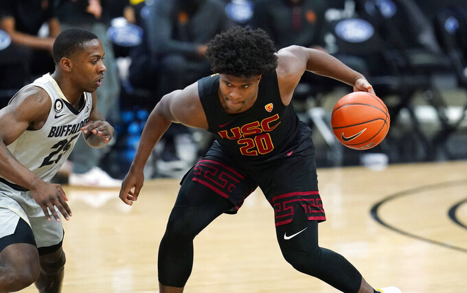 Southern California guard Ethan Anderson, right, is defended by Colorado guard McKinley Wright IV during the first half of an NCAA college basketball game Thursday, Feb. 25, 2021, in Boulder, Colo. (AP Photo/David Zalubowski)