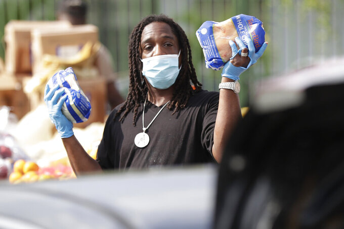 Terry Axson Jr., holds up two chickens as he waits for the next car to pass during a food distribution event, Wednesday, April 1, 2020, in the Liberty City neighborhood of Miami. The event was supported by the city, Ark of the City and Farm Share. (AP Photo/Wilfredo Lee)
