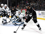 Los Angeles Kings center Anze Kopitar, right, looks to pass during a power play against the San Jose Sharks during the second period of an NHL hockey game, Monday, Nov. 25, 2019, in Los Angeles. (AP Photo/Michael Owen Baker)