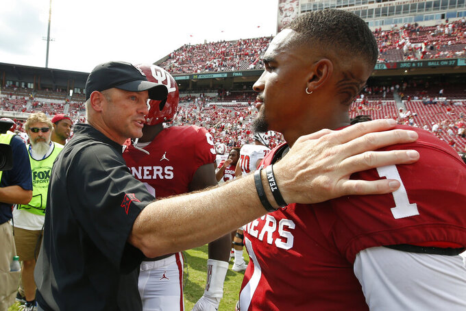 Texas Tech head coach Matt Wells, left, talks with Oklahoma quarterback Jalen Hurts (1) following their NCAA college football game in Norman, Okla., Saturday, Sept. 28, 2019. (AP Photo/Sue Ogrocki)