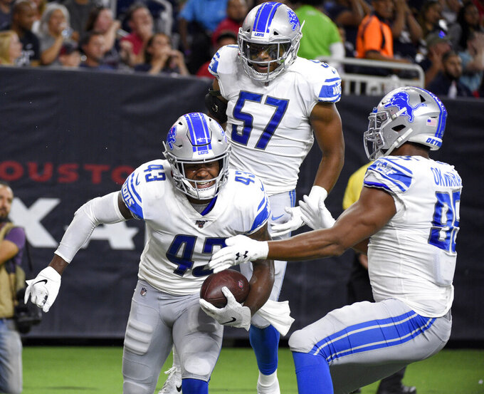 Detroit Lions' Will Harris (43) celebrates with Anthony Pittman (57) and Romeo Okwara after returning a fumble for a touchdown against Houston Texans during the first half of an NFL preseason football game Saturday, Aug. 17, 2019, in Houston. (AP Photo/Eric Christian Smith)