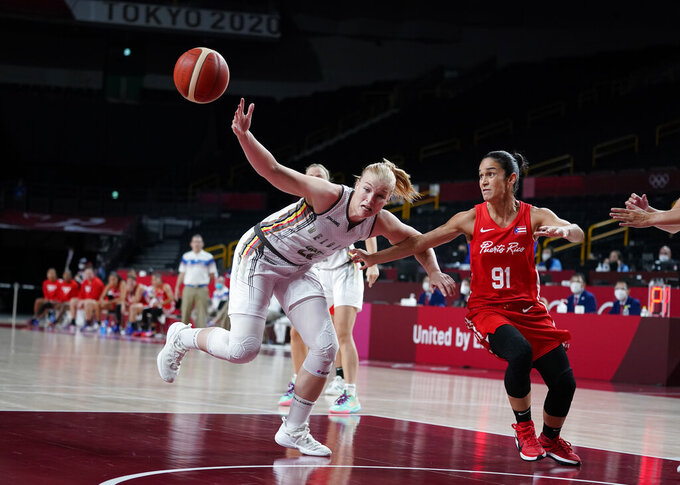 Belgium's Hanne Mestdagh (22), left, and Puerto Rico's Michelle Gonzalez (91) fight for the ball during women's basketball preliminary round game at the 2020 Summer Olympics, Friday, July 30, 2021, in Saitama, Japan. (AP Photo/Charlie Neibergall)
