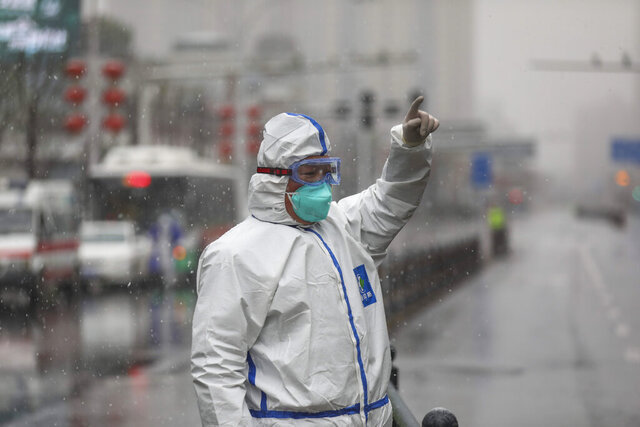 A worker wearing a protective suit gestures to a driver outside a tumor hospital newly designated to treat COVID-19 patients in Wuhan in central China's Hubei Province, Saturday, Feb. 15, 2020. The virus is thought to have infected more than 67,000 people globally and has killed at least 1,526 people, the vast majority in China, as the Chinese government announced new anti-disease measures while businesses reopen following sweeping controls that have idled much of the economy. (Chinatopix via AP)