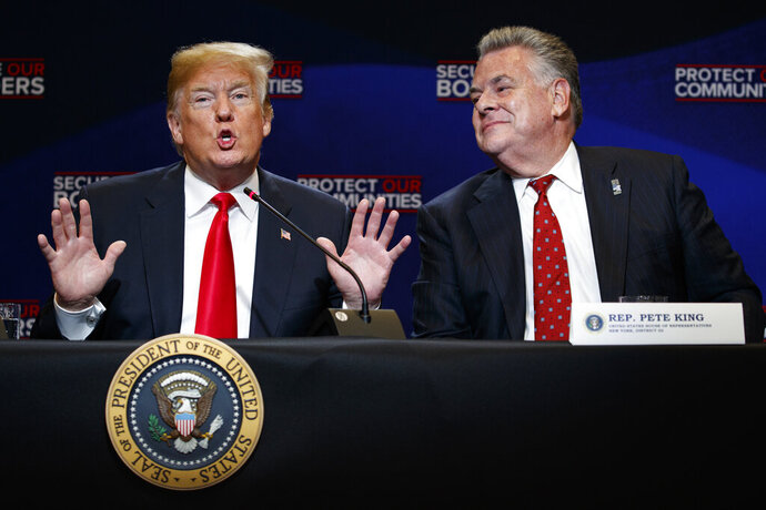FILE - In this May 23, 2018, file photo, Rep. Peter King, R-N.Y., right, listens as President Donald Trump speaks during a roundtable on immigration policy at Morrelly Homeland Security Center in Bethpage, N.Y. King announced Monday, Nov. 11, 2019,  he will not seek reelection in 2020. The 14-term Republican congressman said in a Facebook post that his commute was a main factor in his decision, saying he wants
