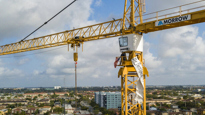 A man stands inside a construction crane where he attached an American flag and a banner near Florida International University in Sweetwater, Fla., Monday, Feb. 18, 2019. President Donald Trump is scheduled to host a rally at the school in the afternoon. (Matias J. Ocner/Miami Herald via AP)