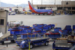 Empty luggage carts sit on the tarmac along with a Southwest Airlines plane at Sky Harbor Airport, Tuesday, March 17, 2020, in Phoenix, as airlines cut flights due to the coronavirus outbreak. (AP Photo/Sue Ogrocki)