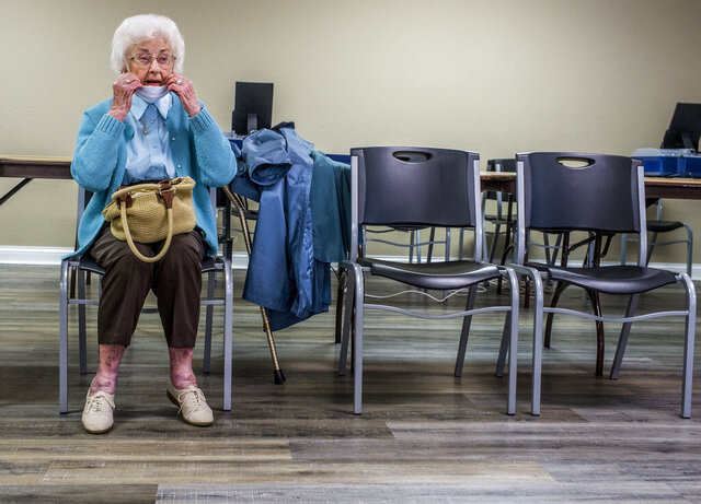 Harriet Harris, 99, of Pekin, Ill., waits her turn during early voting at the Tremont Community Center in Peoria, Ill., Friday, Oct. 23, 2020. Harris has voted in every presidential election since 1944. This year was the first time the lifelong Republican cast a ballot for a Democratic presidential candidate. (David Zalaznik/Journal Star via AP)