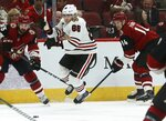 Chicago Blackhawks right wing Patrick Kane (88) gets tripped up by Arizona Coyotes right wing Richard Panik (14) as Coyotes center Brad Richardson (15) looks for the puck during the first period of an NHL hockey game Tuesday, March 26, 2019, in Glendale, Ariz. (AP Photo/Ross D. Franklin)
