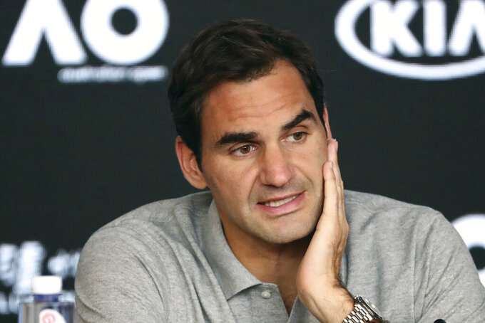 """FILE - In this Jan. 30, 2020, file photo, Switzerland's Roger Federer speaks during a press conference following his semifinal loss to Serbia's Novak Djokovic at the Australian Open tennis championship in Melbourne, Australia. Federer has raised the prospect of merging the governing bodies that oversee the men's and women's professional tennis tours. The 20-time Grand Slam champion began a string of posts on Twitter by saying the shutdown of tennis because of the coronavirus outbreak has given the sport an ideal opportunity to assess its future. Federer says it might be """"the time for men's and women's tennis to be united and come together as one."""" (AP Photo/Dita Alangkara, File)"""