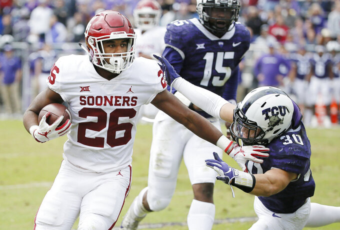 Oklahoma running back Kennedy Brooks (26) battles past TCU linebacker Garret Wallow (30) to score a touchdown during the first half of an NCAA college football game, Saturday, Oct. 20, 2018, in Fort Worth, Texas. Oklahoma won 52-27. (AP Photo/Brandon Wade)