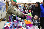 This Dec. 3, 2019, photo shows Alaska National Guard Staff Sgt. Joseph Sallaffie handing a gift bag to Corban Jimmy while Marlene Black looks on during Santa's visit to Napakiak, Alaska. The Alaska National Guard brought its Operation Santa Claus to the western Alaska community, which is being severely eroded by the nearby Kuskokwim River. (AP Photo/Mark Thiessen)