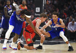 Atlanta Hawks guard Trae Young, center, works for the ball between Los Angeles Clippers forward Montrezl Harrell, left, and guard Jerome Robinson during the first half of an NBA basketball game in Los Angeles, Saturday, Nov. 16, 2019. (AP Photo/Kelvin Kuo)