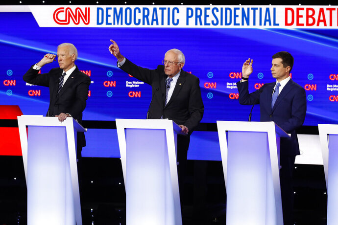 FILE - In this Tuesday, Jan. 14, 2020 file photo, from left, Democratic presidential candidate former Vice President Joe Biden, Sen. Bernie Sanders, I-Vt.,and former South Bend Mayor Pete Buttigieg look to answer a question during a Democratic presidential primary debate hosted by CNN and the Des Moines Register in Des Moines, Iowa. Multiple Democratic presidential hopefuls have talked about their faith on the campaign trail, weaving it into their approach to issues from immigration to climate change. Among the most vocal Democrats on that front is Buttigieg, who asserted his party's connection to religion on Tuesday during its final primary debate before next month's first-in-the-nation Iowa caucus. (AP Photo/Patrick Semansky, File)