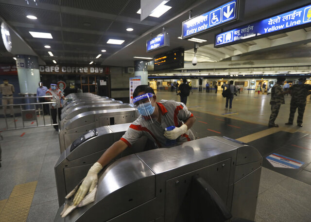 A workers sanitizes a metro station in New Delhi, India, Thursday, Sept. 3, 2020. Delhi Metro will open its services in a phased manner from Sept. 7, even as India has been reporting the highest single-day caseload in the world every day for more than three weeks and is the third worst-hit country behind the United States and Brazil. The country's economy contracted by 23.9% in the April-June quarter, India's worst performance in at least 24 years.(AP Photo/Manish Swarup)