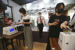 Christians wearing face masks to help protect against the spread of the new coronavirus scan QR codes on their smartphones before attending a service at the Yoido Full Gospel Church in Seoul, South Korea, Sunday, July 5, 2020. (AP Photo/Ahn Young-joon)