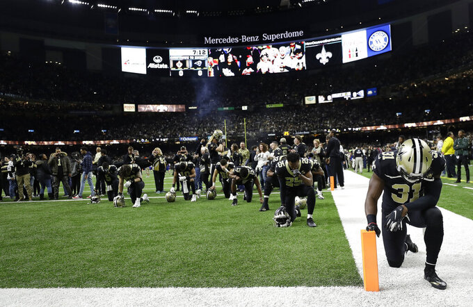 New Orleans Saints' Chris Banjo kneels with teammates before the NFL football NFC championship game against the Los Angeles Rams, Sunday, Jan. 20, 2019, in New Orleans. (AP Photo/David J. Phillip)