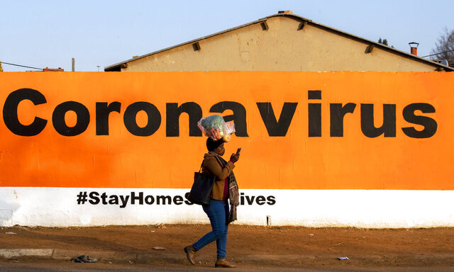 FILE - In this Friday June 19, 2020, a woman wearing a face mask passes a coronavirus billboard carrying a message in a bid to prevent the spread of the virus.  South Africa's Health Minister Zwelini Mkhize said Sunday June 28, 2020 the country's current surge of COVID-19 cases is expected to dramatically increase in the coming weeks and press the country's hospitals to the limit. (AP Photo/Themba Hadebe/File)