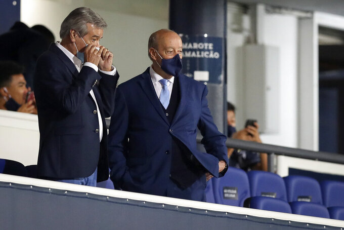 Porto's president Jorge Nuno Pinto da Costa, center, looks to the pitch from the stands before the start of the Portuguese League soccer match between FC Famalicao and FC Porto in Famalicao, Portugal, Wednesday, June 3, 2020. The Portuguese League soccer matches resumed Wednesday without spectators because of the coronavirus pandemic. (Jose Coelho/Pool via AP)