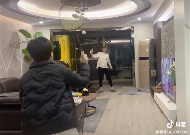 In this Tuesday, Jan. 28, 2020, image from video posted on Douyin, a popular Chinese social media platform, Wei Zikai's family plays badminton in the living room of their home in Wuhan, China. Chinese around the country confined to their apartments either by choice or by order are making the best of the situation as cities remain in lockdown in a desperate bid to contain a new, dangerous virus. (Douyin user Wei Zikai via AP)