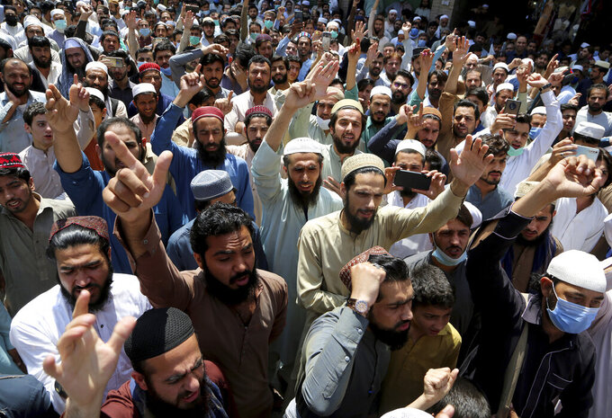 Traders chant slogans at a rally to condemn the security forces's crackdown against a banned Tehreek-e-Labaik Pakistan party, in Peshawar, Pakistan, Monday, April 19, 2021. An outlawed Pakistani Islamist political group freed 11 policemen almost a day after taking them hostage in the eastern city of Lahore amid violent clashes with security forces, the country's interior minister said Monday. (AP Photo/Muhammad Sajjad)