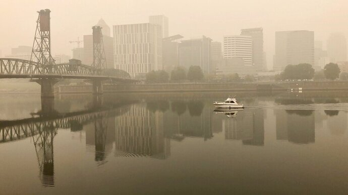 A view of downtown Portland from the East Bank Esplanade is seen on Monday, Sept. 14, 2020. The entire Portland metropolitan region remains under a thick blanket of smog from wildfires that are burning around the state and residents are being advised to remain indoors due to hazardous air quality. (AP Photo/Gillian Flaccus)
