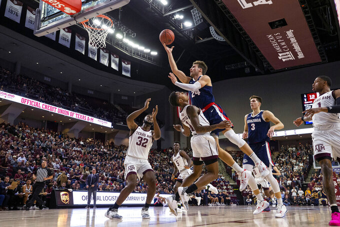 Texas A&M guard Wendell Mitchell (11) draws a charing foul against Gonzaga forward Corey Kispert (24) during the first half of an NCAA college basketball game Friday, Nov. 15, 2019, in College Station, Texas. (AP Photo/Sam Craft)