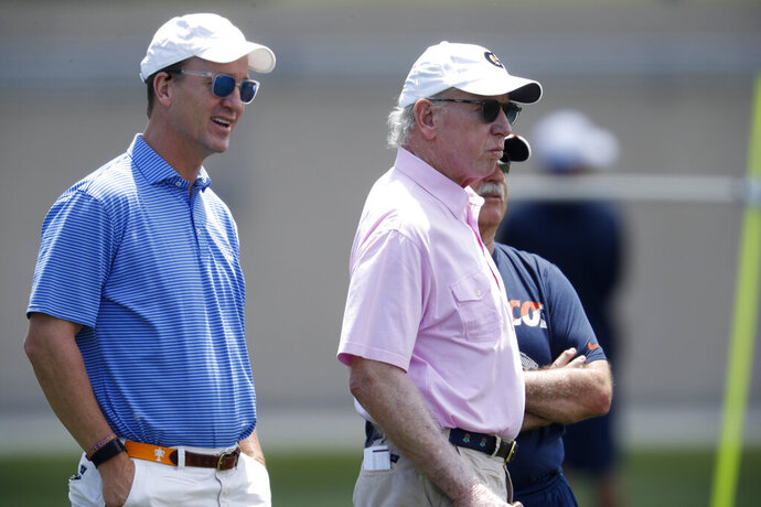 Former NFL quarterbacks Peyton Manning, left, and his father, Archie watch the Denver Broncos take part in drills at the team's NFL football training facility Wednesday, June 5, 2019, in Englewood, Colo. (AP Photo/David Zalubowski)
