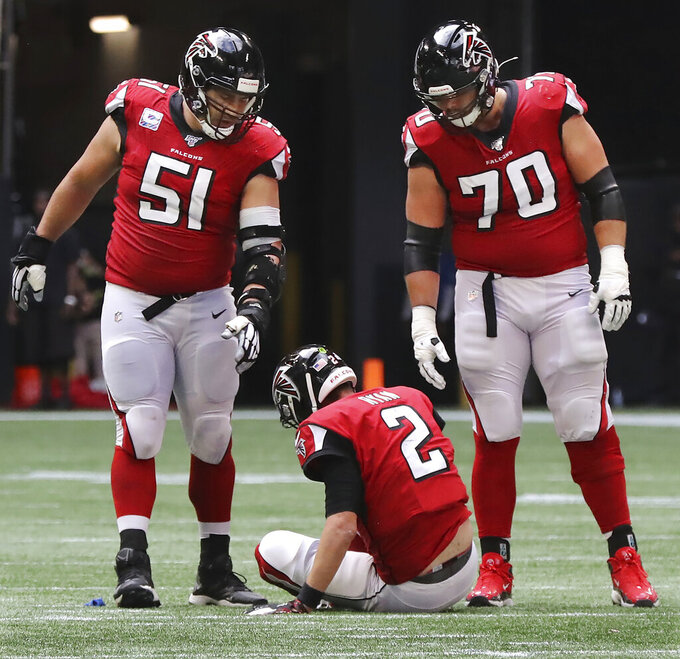 Atlanta Falcons quarterback Matt Ryan (2) sits on the field with Alex Mack (51) and Jake Matthews (70) looking on after Los Angeles Rams defensive tackle Aaron Donald leveled him, causing a fumble that the Rams recovered, in the fourth quarter of an NFL football game Sunday, Oct. 20, 2019, in Atlanta. Ryan left the game with an apparent leg injury. (Curtis ComptonAtlanta Journal-Constitution via AP)