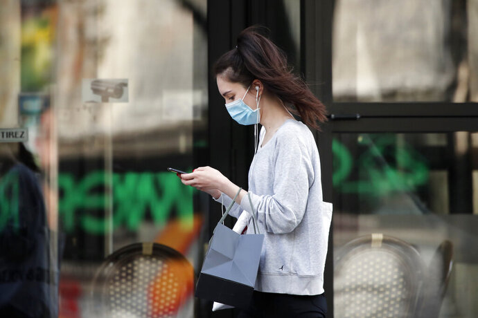 FILE - In this photo taken on April 20, 2020, a woman wearing protective face mask looks at her phone past a closed restaurant during a nationwide confinement to counter the COVID-19, in Paris. French lawmakers are set to vote on whether allowing or not France's contact-tracing app designed to contain the spread of the coronavirus that is raising privacy concerns. (AP Photo/Francois Mori, File)