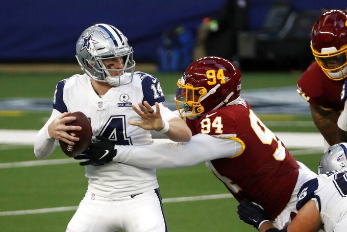 Dallas Cowboys quarterback Andy Dalton (14) is wrapped up by Washington Football Team defensive tackle Daron Payne (94) in the first half of an NFL football game in Arlington, Texas, Thursday, Nov. 26, 2020. (AP Photo/Roger Steinman)