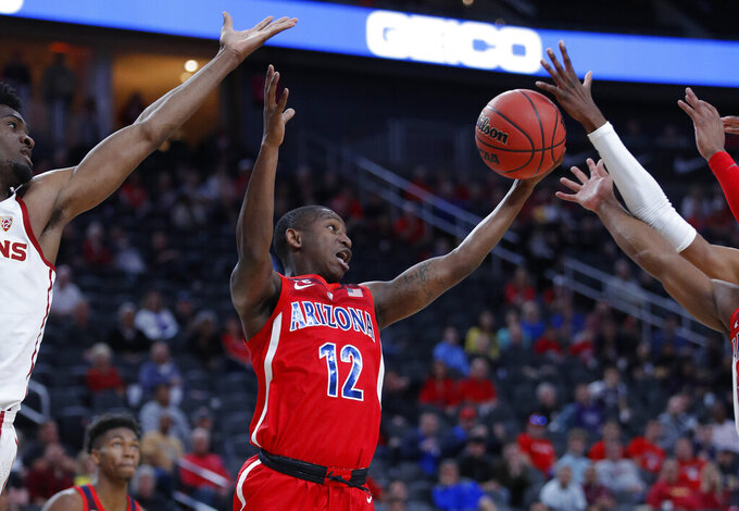 Arizona's Justin Coleman grabs a rebound against Southern California during the first half of an NCAA college basketball game in the first round of the Pac-12 conference tournament Wednesday, March 13, 2019, in Las Vegas. (AP Photo/John Locher)