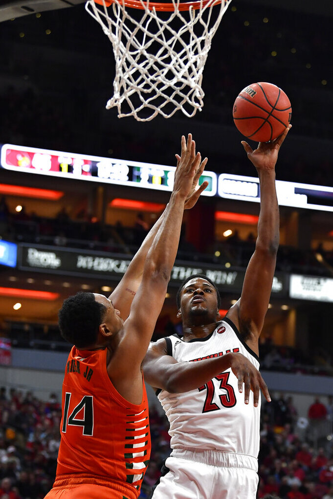 Louisville center Steven Enoch (23) shoots over Miami center Rodney Miller Jr. (14) during the second half of an NCAA college basketball game in Louisville, Ky., Tuesday, Jan. 7, 2020. Louisville won 74-58. (AP Photo/Timothy D. Easley)