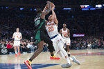 New York Knicks forward Kevin Knox (20) lands on his ankle as he drives to the basket against Boston Celtics guard Terry Rozier (12) during the first half of an NBA basketball game, Saturday, Oct. 20, 2018, at Madison Square Garden in New York. (AP Photo/Mary Altaffer)