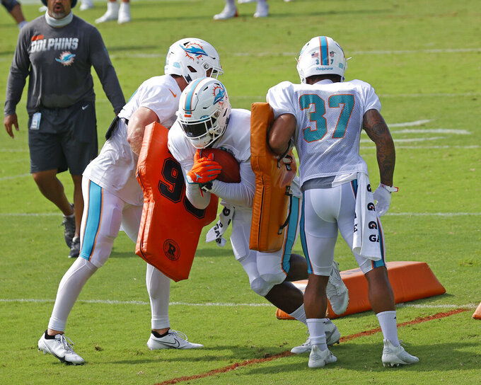 Miami Dolphins running back Patrick Laird (32), left, running back Jordan Howard (34), center, and running back Myles Gaskin (37) run a drill during an NFL football training camp practice in Davie, Fla., Monday, Aug. 17, 2020. (AP Photo/Joel Auerbach)
