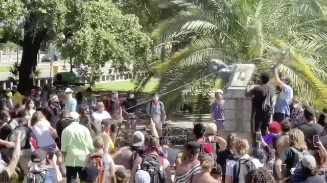 In this frame grab from video posted on Twitter, protesters bring down a bust of slave owner John McDonogh, Saturday, June 13, 2020, at Duncan Plaza in New Orleans. The protesters then took the remains to the Mississippi River and rolled it into the water. The destruction is part of a nationwide effort to remove monuments to the Confederacy or with links to slavery as the country grapples with widespread protests against police brutality toward African Americans. (Twitter via AP)