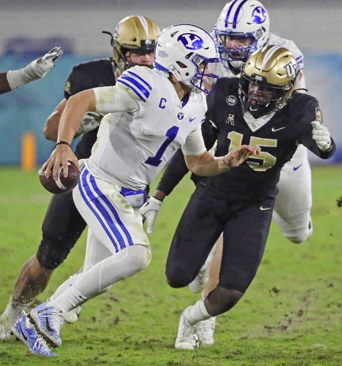 UCF linebacker Tatum Bethune (15) chases BYU quarterback Zach Wilson (1) in the fourth quarter in the Boca Raton Bowl NCAA college football game at FAU Stadium in Boca Raton, Fla. Tuesday, Dec. 22, 2020.(Al Diaz/Miami Herald via AP)