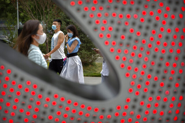People wearing face masks to protect against the spread of the new coronavirus walk through a shopping and office complex in Beijing, Wednesday, June 24, 2020. New virus cases have declined in China and in the capital Beijing, where a two-week spike appears to be firmly waning. (AP Photo/Mark Schiefelbein)